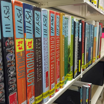 A row of textbooks line Library shelves in reserve.