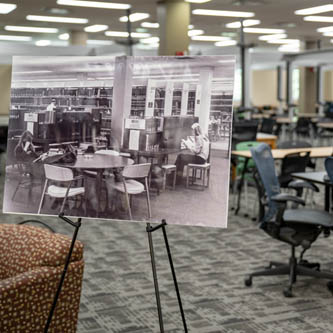 A printed sign on an easel in modern King Library's first floor displays a black and white image of King Library in the past
