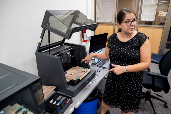 Creation and innovation services librarian Sarah Nagle gestures at a Carvey CNC routing machine in the new Makerspace in King Library